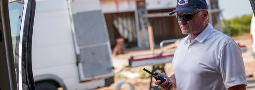 Older man using two-way radio at a construction site