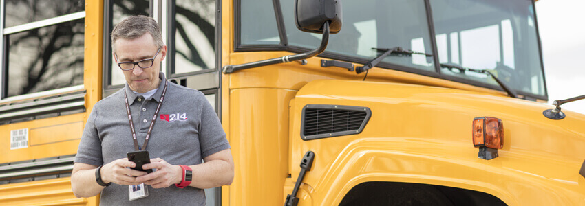Man on phone in front of school bus