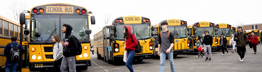 Kids walking past a row of buses in the parking lot