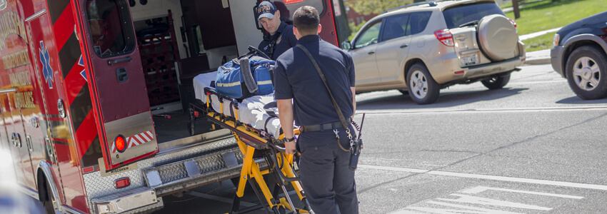 Two EMT's lifting a stretcher into an ambulance