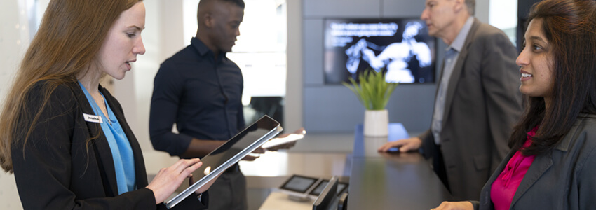 Workers behind desk at hotel speaking with guests using tablets