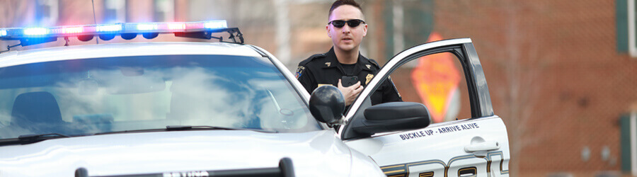 Officer using two-way radio as he gets out of his police car