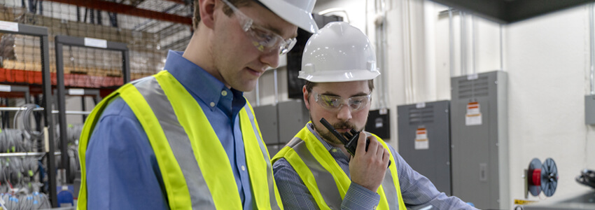 Two men in a warehouse using a two-way radio