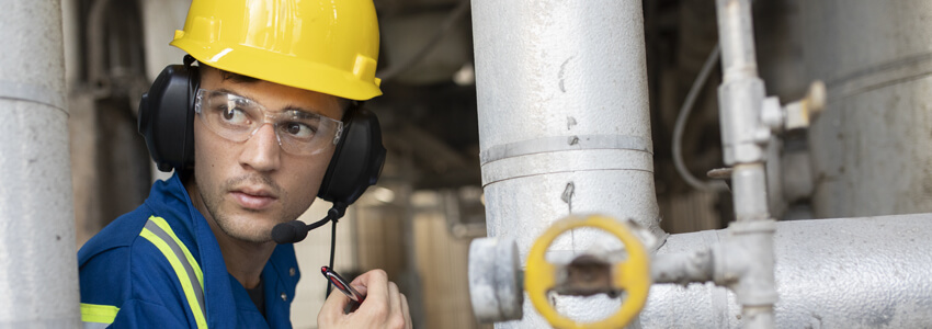 Man near pipes using a headset