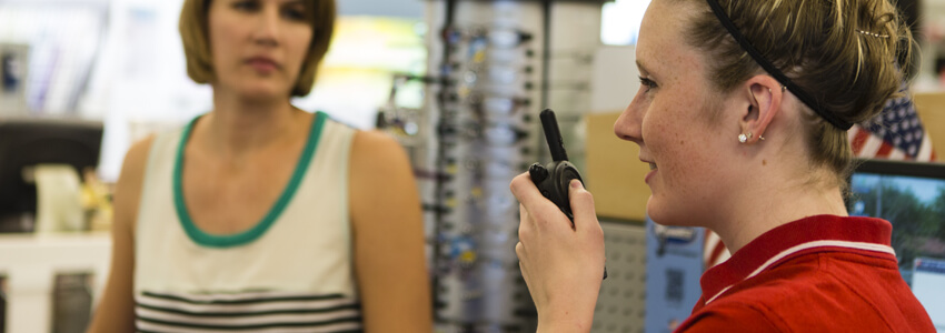 Retail worker using a two-way radio in front of a customer