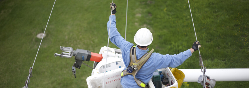 Lineman in a bucket truck up in the air holding onto power lines